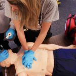 Students wearing gloves give mannequin CPR