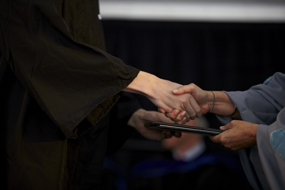 hands shaking and handing diploma