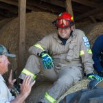 Fire fighter in protective gear sitting on hay bale