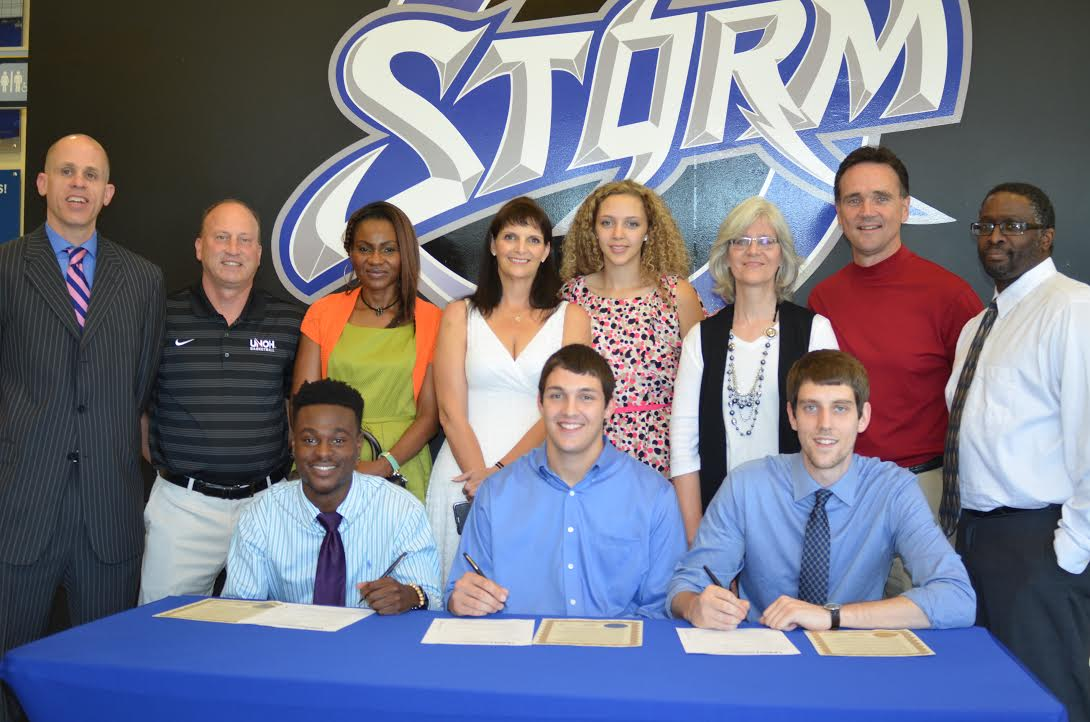 Three players signing with supportive group behind them