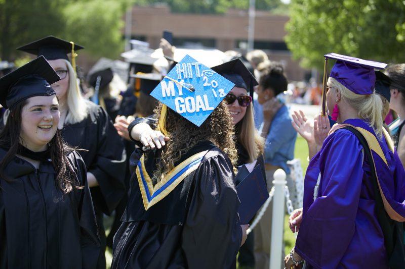 "Recent DCCC graduates hug with top of cap reading ""Hit my goal 2018"""
