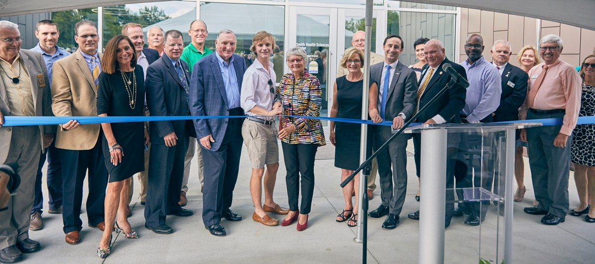 Large group of DCCC leaders pose ready to cut ribbon of new building.