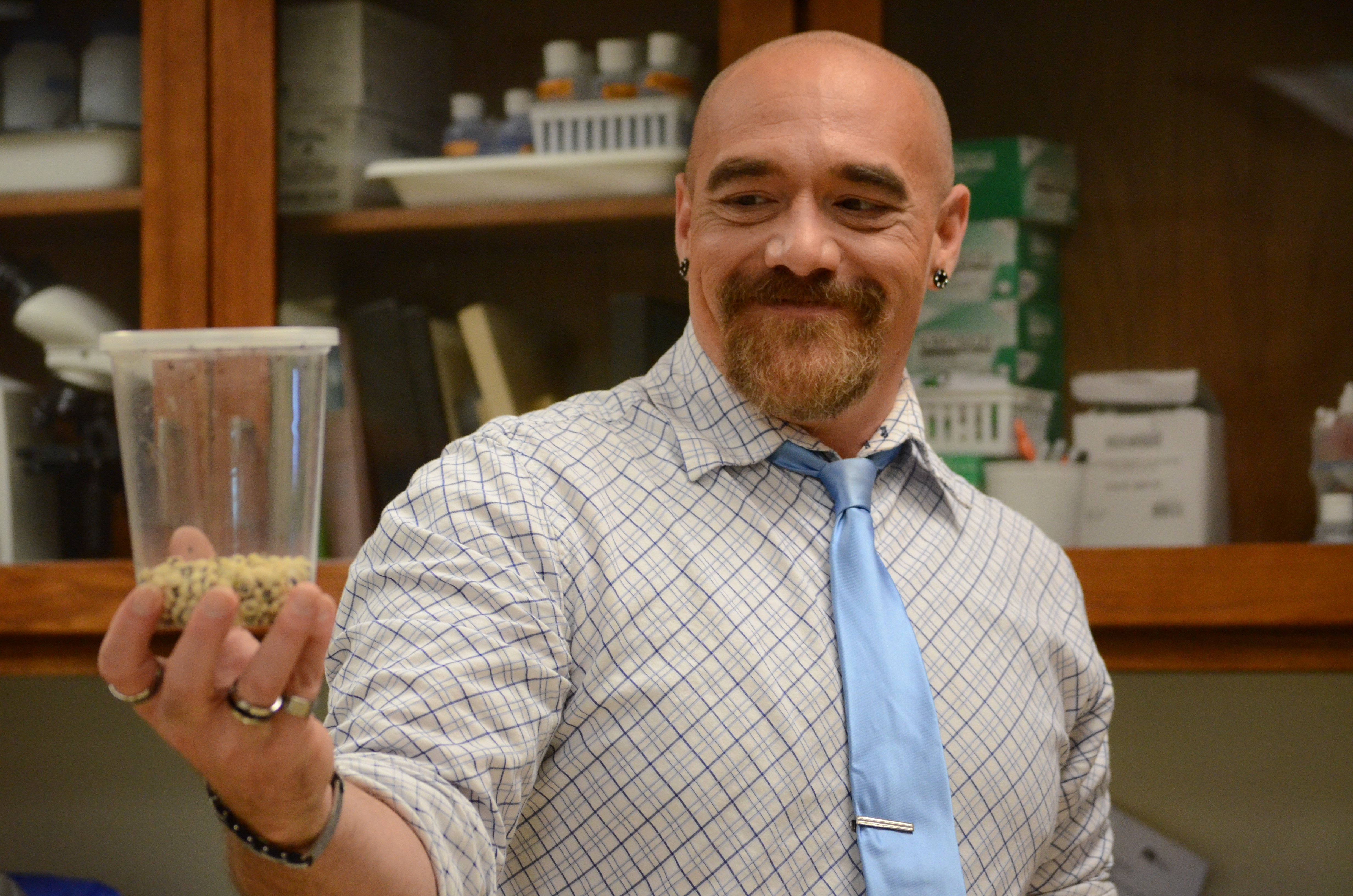 Instructor Joe Felts holds a concealed cup of insects.