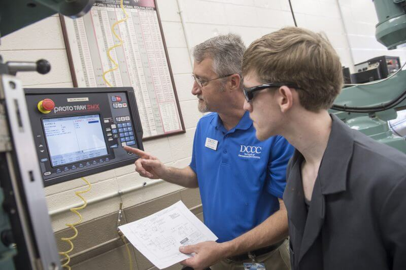 Instructor shows student how to use machine equipment.