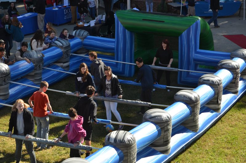 Students playing Human-sized inflatable foosball.