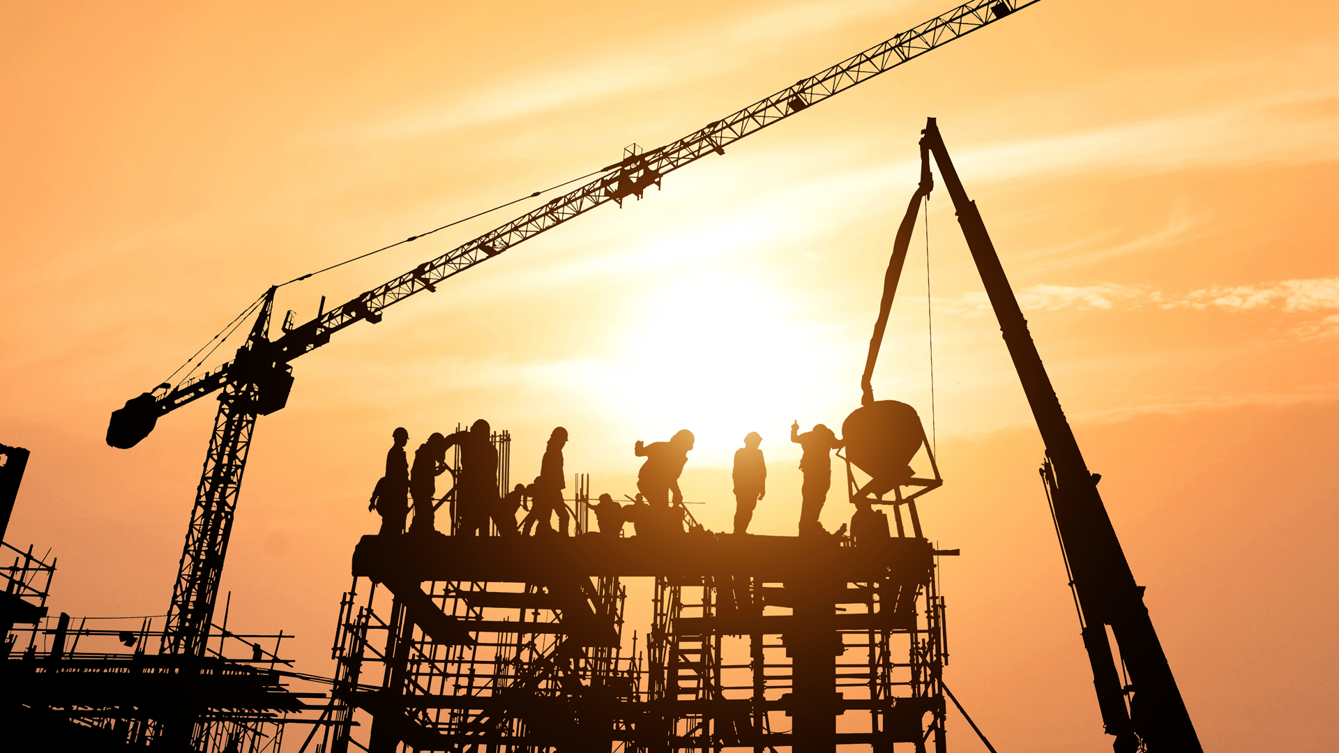 Workers on skyscraper being built with sun setting in background