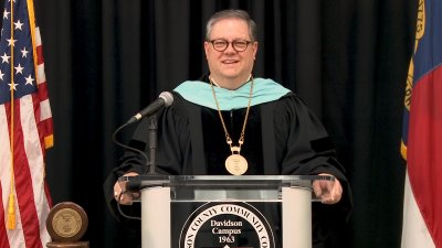 Darrin Hartness at lecturn between American and North Carolina flags in graduation robes.