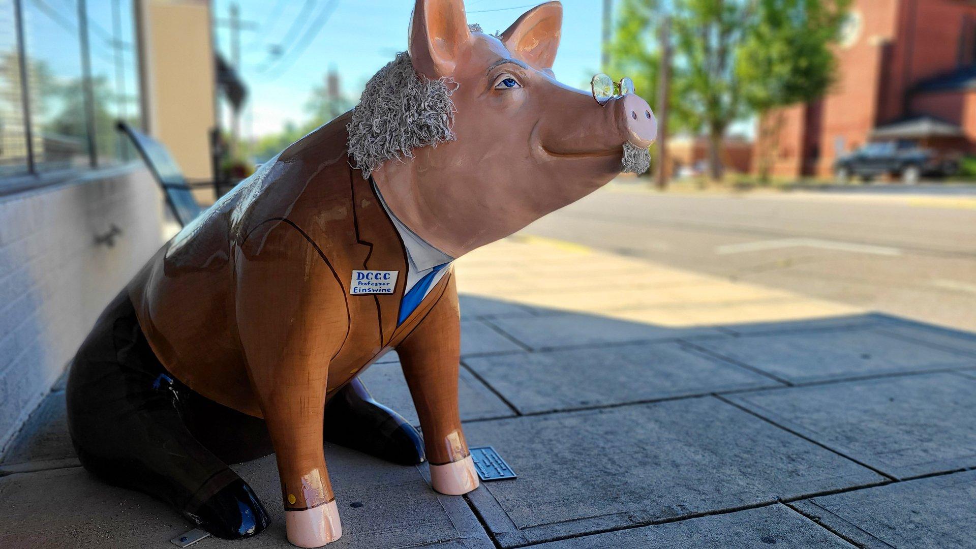 Pig Statue on sidewalk. Text reads: DCCC professor Einswine