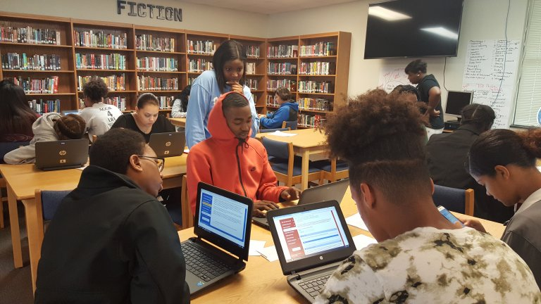 Students working on laptops in a library