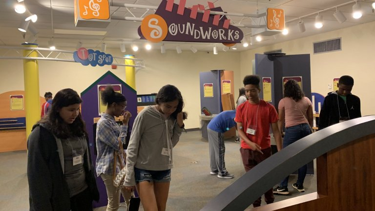 Group of TRIO Students interacting with exhibits in a museum