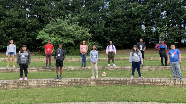 Group of TRIO Students standing on various levels of a amphitheater seating area