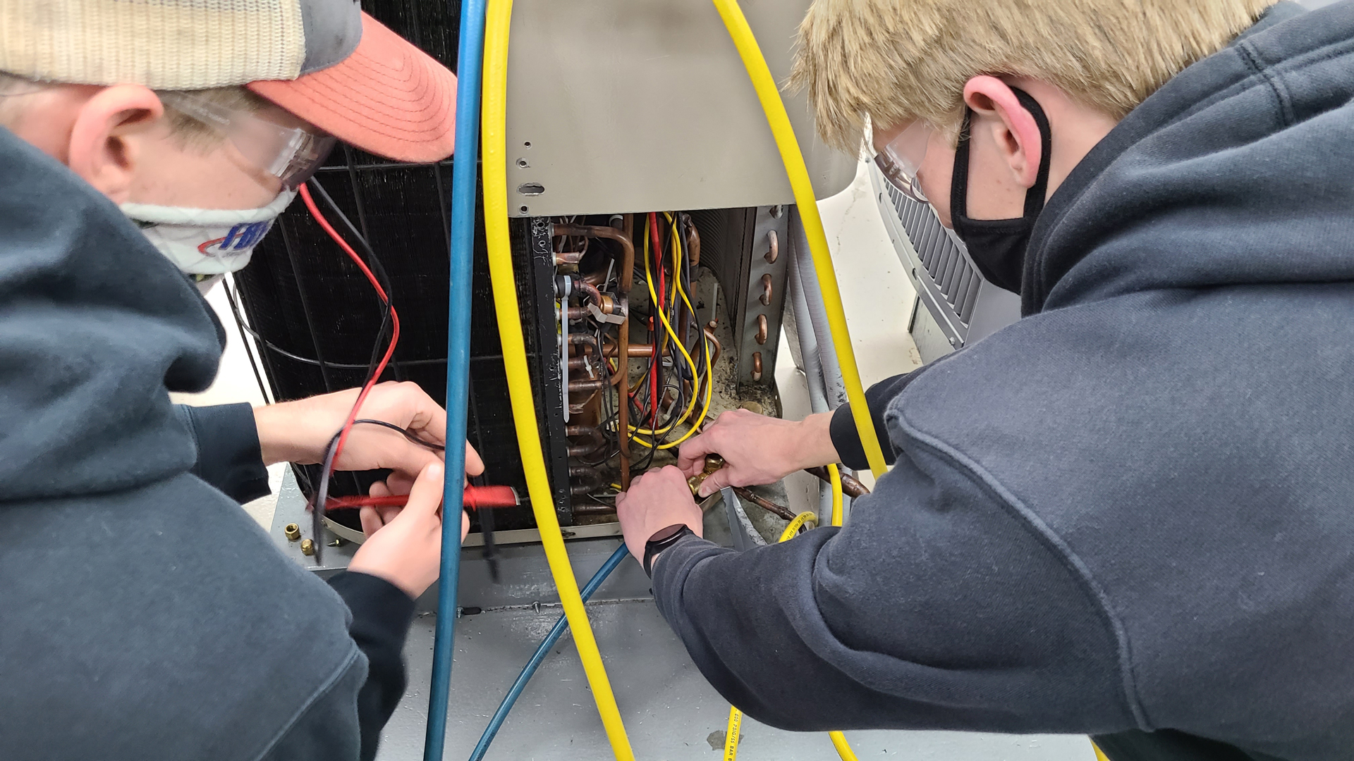 Two male HVAC Students look at wiring of HVAC unit
