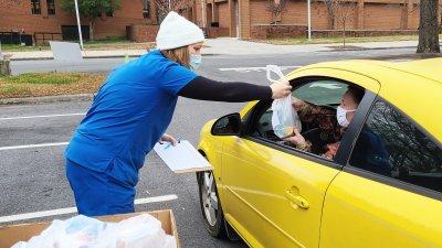 Volunteer handing bag of medicine to driver of yellow car