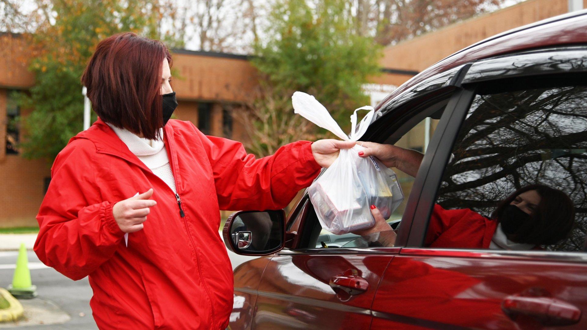 Volunteer in red coat handing bag of medicine to driver ofred car