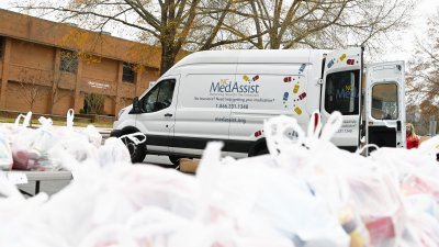 Plastic bags of medicine organized to be given away. MedAssist van in background.