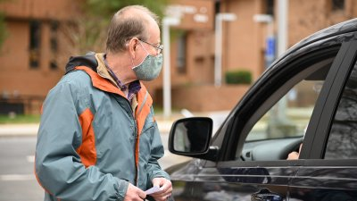 volunteer gathering information from driver of car