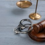 Gavel and Handcuffs on gray table