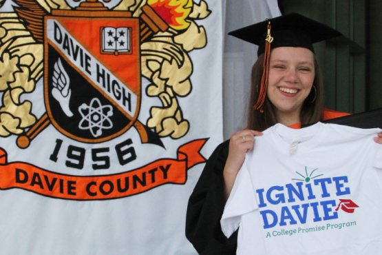 Cassidy Kluttz holding up Ignite Davie shirt in front of Davie County High School banner