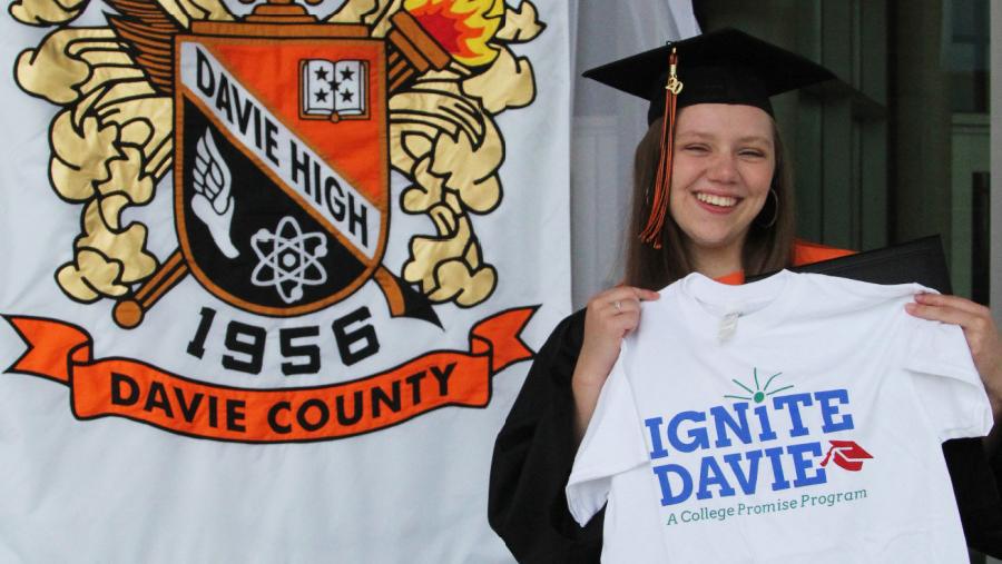 Cassidy Kluttz holding up Ignite Davie shirt in front of Davie County High School banner