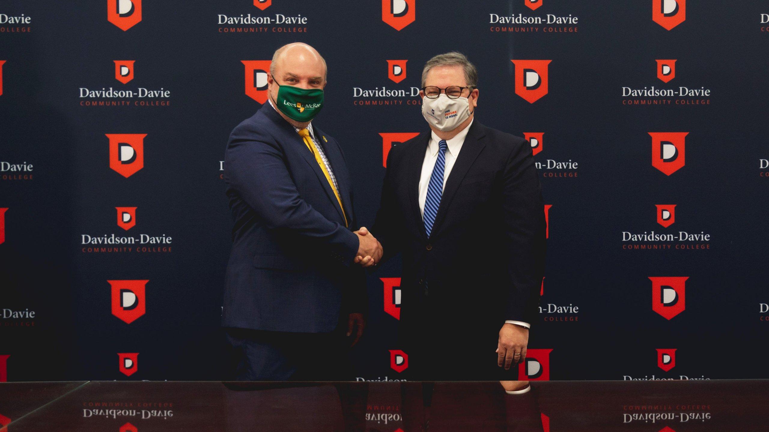 Dr. Hartness & Lees Mcrae representative shaking hands in front of backdrop