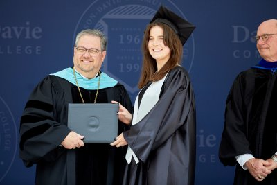 Dr. Darrin Hartness posing for photo with graduate holding a diploma