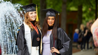 Two graduates in cap and gown in courtyard