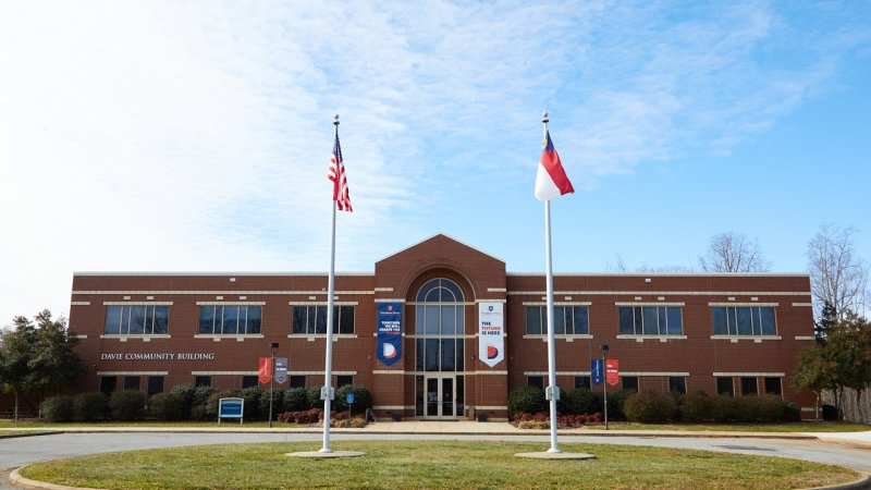 Davie Campus Community Building with flag poles in front
