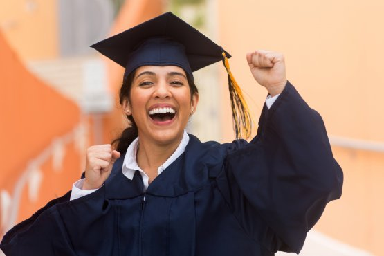 Graduate in cap and gown cheers in excitement