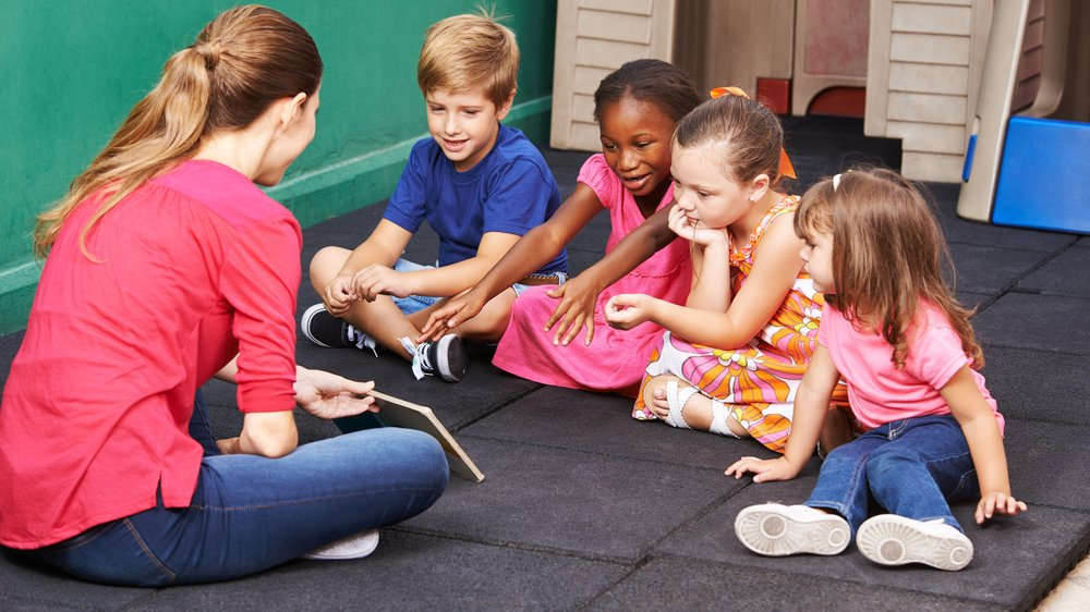 Young teacher sitting on floor with 4 young children