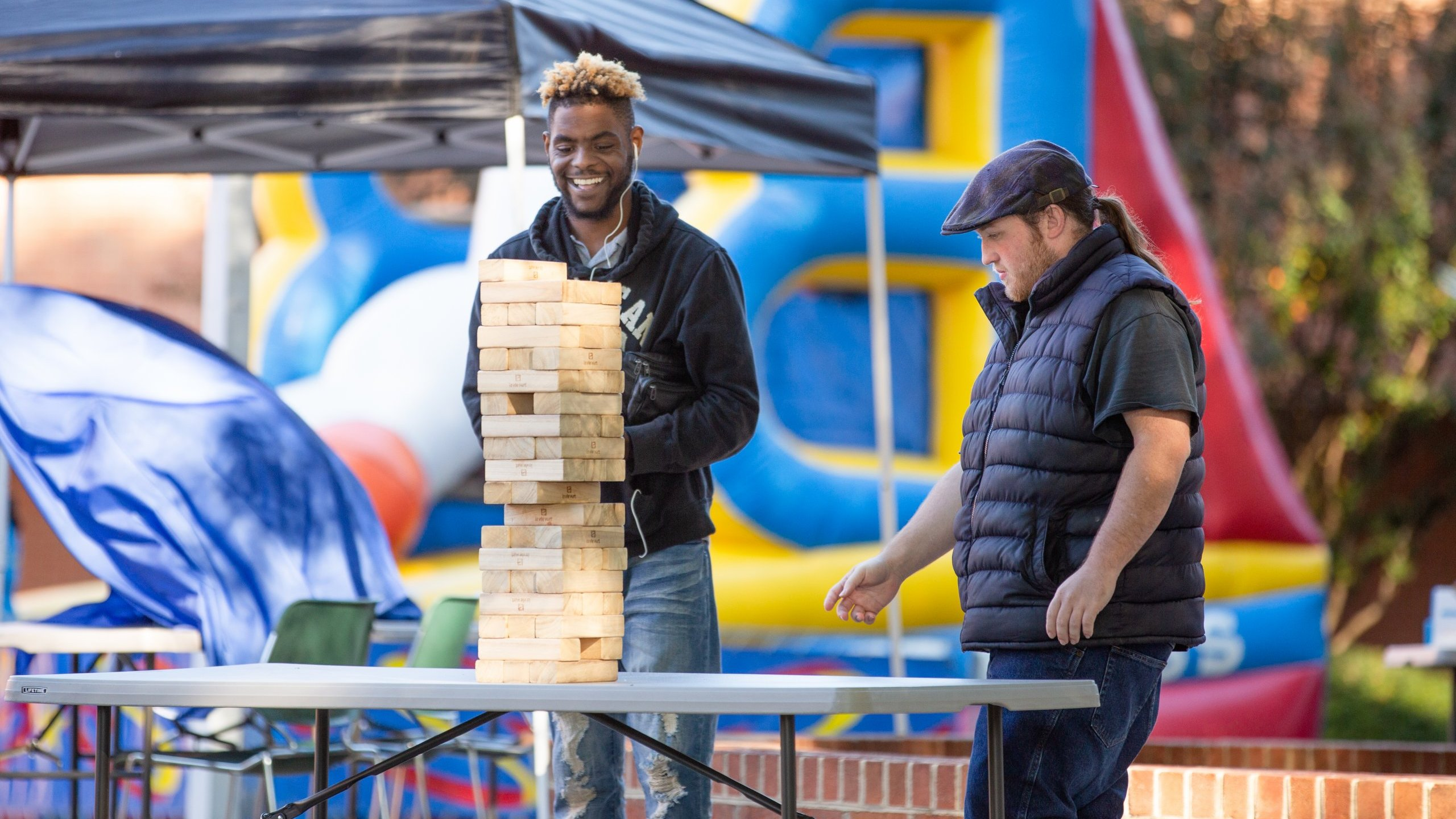 Two college students playing with oversized Jenga blocks