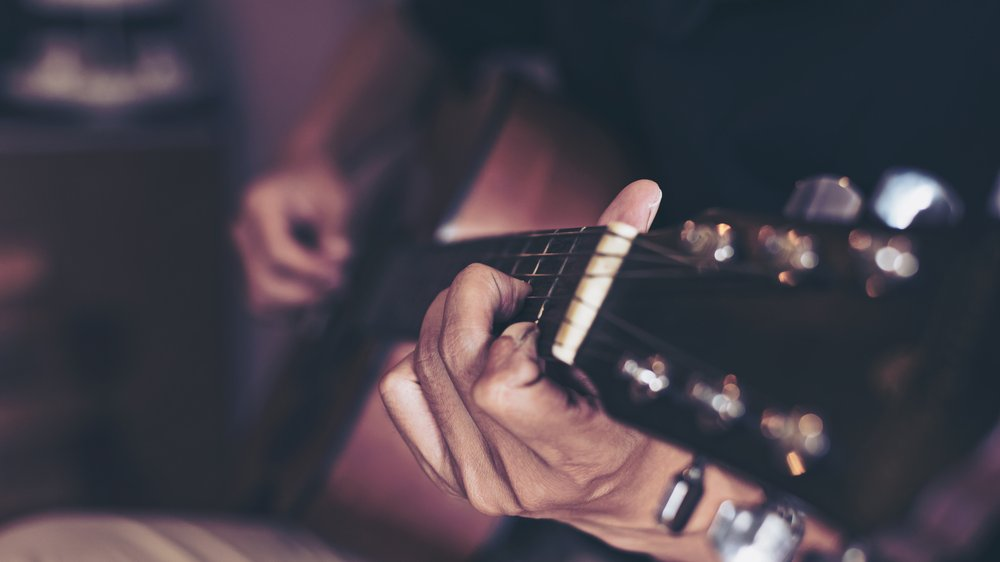 closeup of person holding guitar